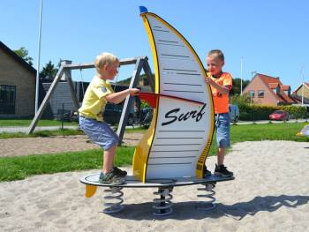 Spring seesaw Windsurfer yellow on the playground with 2 little surfboys