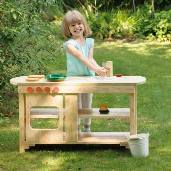Garden play kitchen made of wood with happy playing girl in the garden