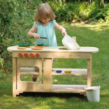 Garden play kitchen made of wood with playing little girl outdoor