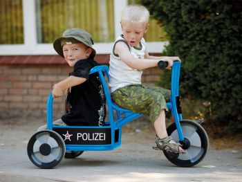 Trycicle Police aktiv with happy playing children on the playground