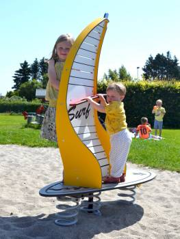 Spring seesaw Windsurfer yellow on the playground with the youngest little surfer