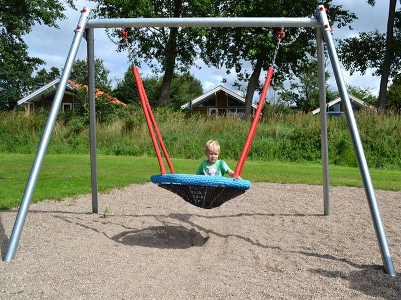 birds-nest-swing on the playground with swinging child