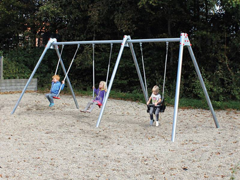 Triple swing with happy swinging children on the plaground