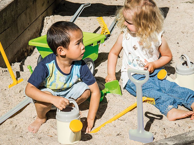 Green Garden Set with happy playing children in the sandbox