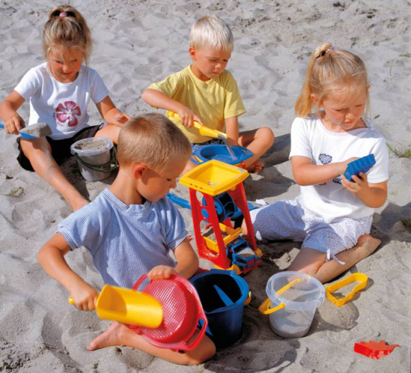 Kindergarten sand set with happy playing children in the sandbox