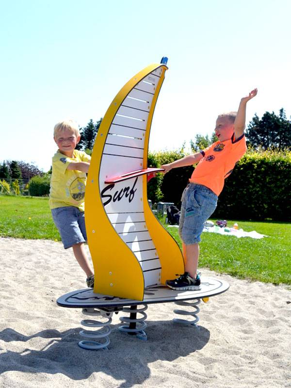 Spring seesaw Windsurfer yellow on the playground with happy playing children
