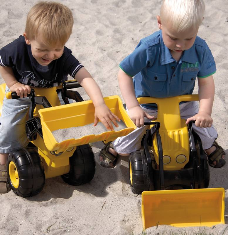 Big wheel loader with happy little kids in the sandbox